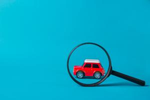 czerwony samochód zaparkowany miniaturka model podlupą tło niebieskie